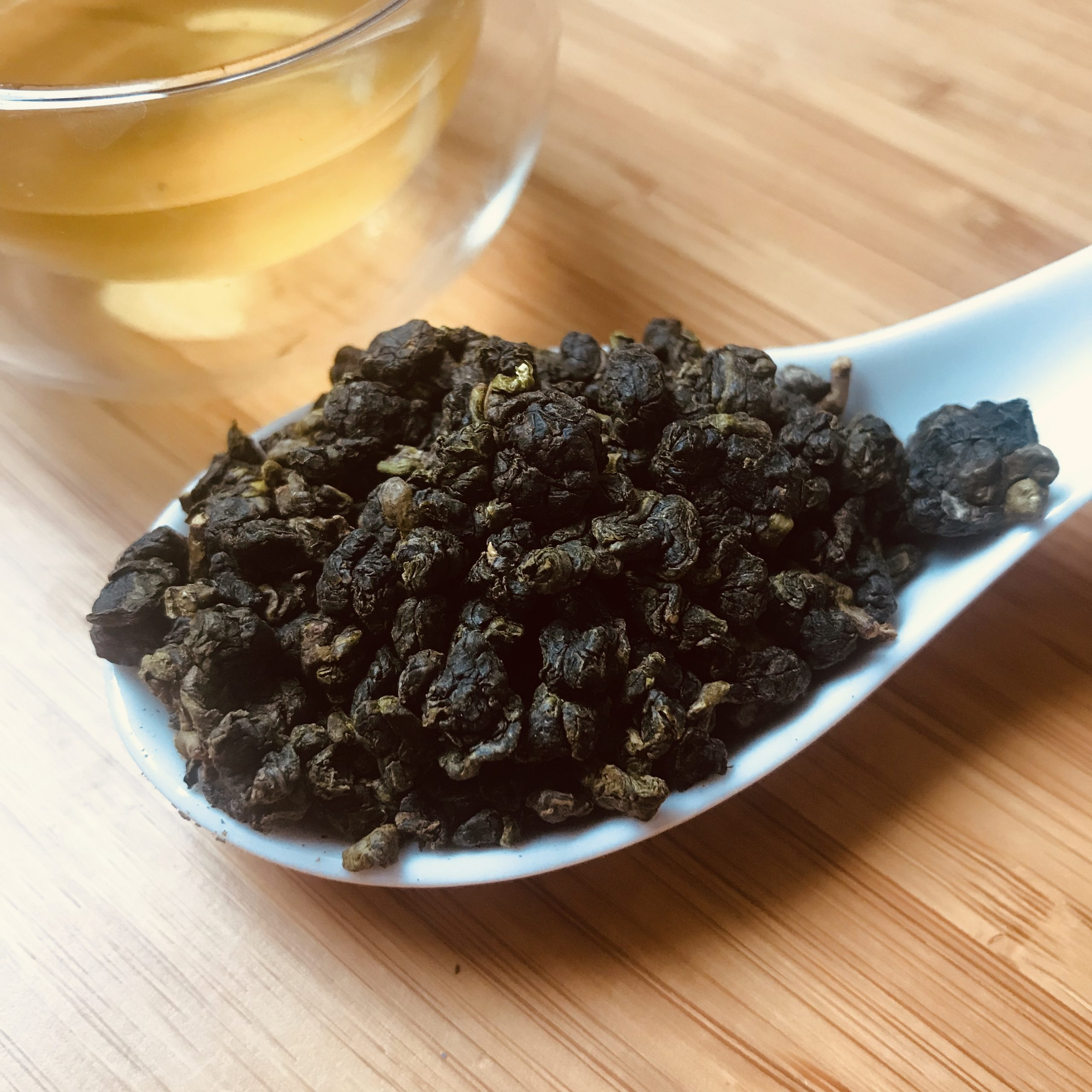 Loose High mountain green tea in rolled bold pellets on a spoon
